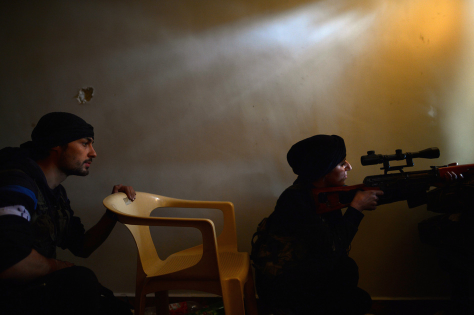 A Syrian female rebel monitors the movement of Syrian government forces in the Sheikh Maqsud district of the northern Syrian city of Aleppo in April. Dimitar Dilkoff /AFP/Getty Images