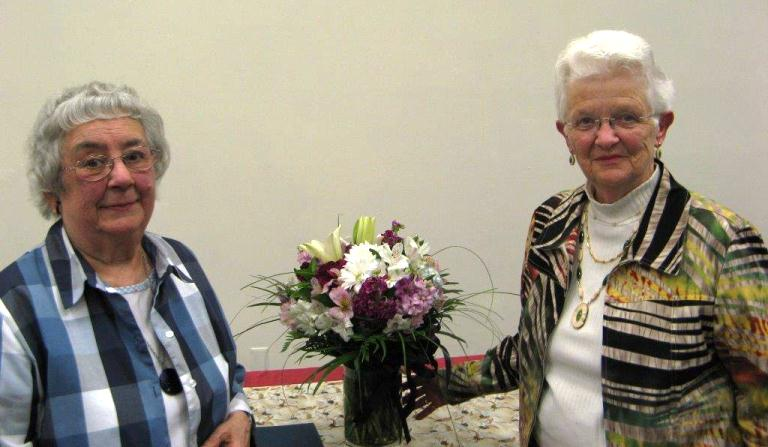 Marie Darlin (left) was honored by the CBJ Assembly for her many years of volunteer service in Juneau.  AARP's Liz Lucas (right) also presented flowers to Darlin. Photo courtesy Liz Lucas.