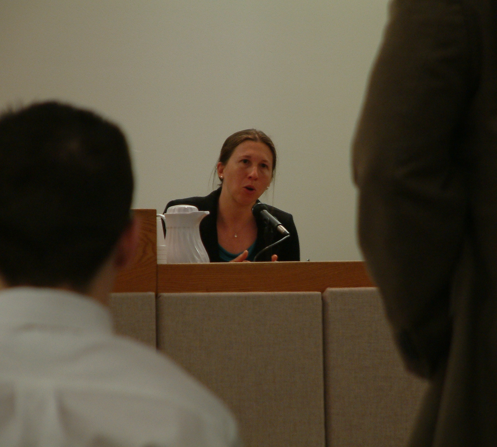 Midwife and advanced nurse practitioner Rebecca Van de Water answers a question posed by public defender Eric Hedland (right foreground) during the trial of David Paul (sitting right foreground with back to camera). Photo by Matt Miller/KTOO News