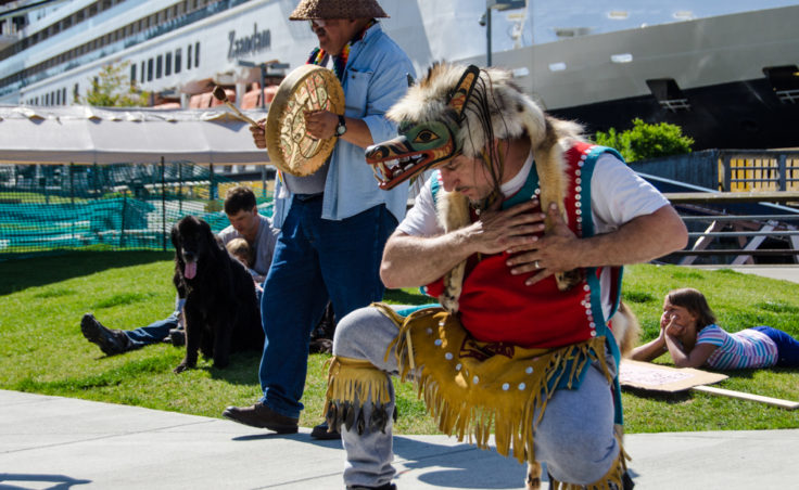 John Smith the 3rd kneels during a dance. (Photo by Heather Bryant/KTOO)