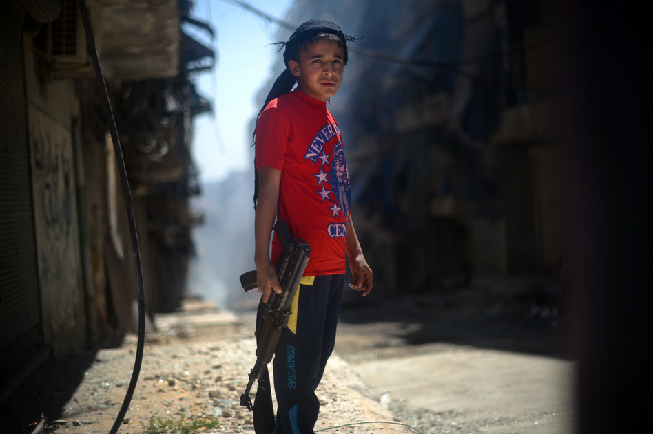 A Syrian boy holds an AK-47 assault rifle in the majority-Kurdish Sheikh Maqsud district of the northern Syrian city of Aleppo in April. Dimitar Dilkoff /AFP/Getty Images