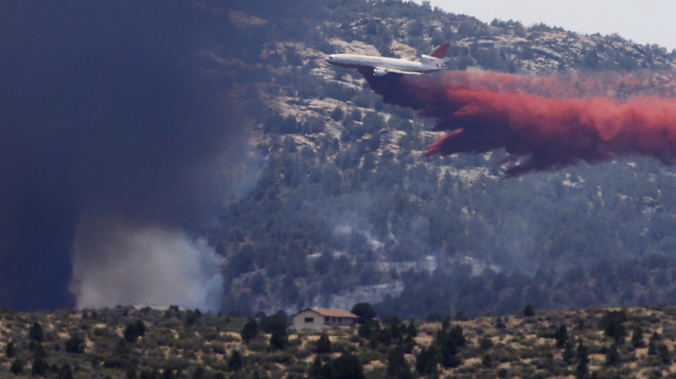 An aerial tanker drops fire retardant on a wildfire threatening homes near Yarnell, Ariz., on July 1. An elite crew of firefighters was overtaken by the out-of-control blaze on June 30, killing 19 members as they tried to protect themselves from the flames under fire-resistant shields. Chris Carlson/AP