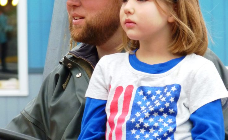 Patriotic young lady with her miner father in the Juneau parade.