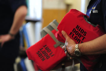 Lt. Tom Pauser, with the 17th Coast Guard District's prevention division, displays two life jackets while discussing their proper use with students at Hogarth Kingeekuk Sr. Memorial School April 10, 2012. The Coast Guard partnered with Alaska's Office of Boating Safety to educate students in rural villages about cold-water safety. U.S. Coast Guard photo by Petty Officer 3rd Class Grant DeVuyst.