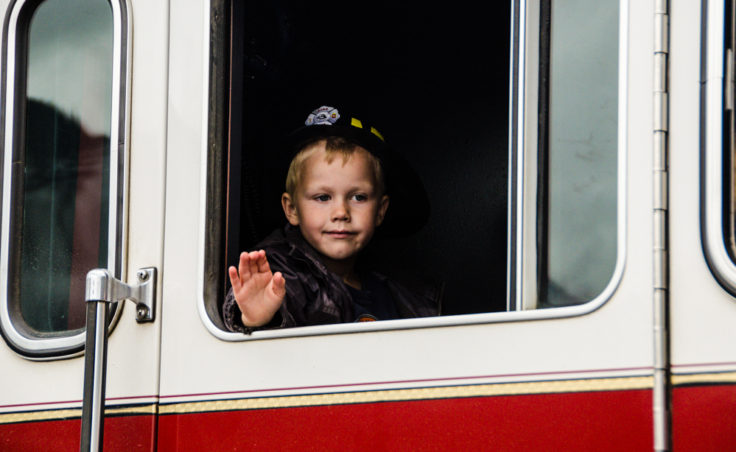 A young boy in a fireman's hat waves from the window of a Juneau fire truck.