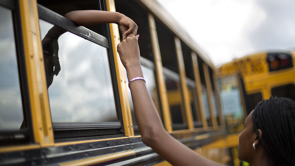 Laterrica Luther, right, holds the hand of her 6-year-old nephew Jaden Culpepper, as students from the Ronald E. McNair Discovery Learning Academy arrive on school buses to waiting loved ones in a Walmart parking lot Tuesday in Decatur, Ga. A gunman had entered the students' school earlier in the day. No one was hurt. David Goldman/AP