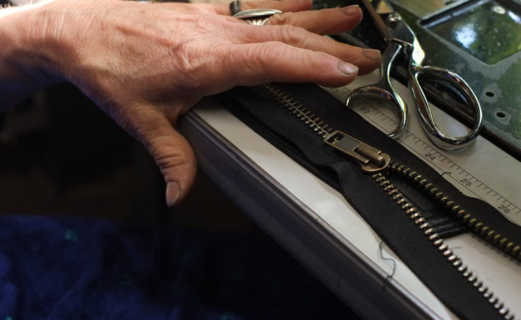 A picture of a hand working on a zipper