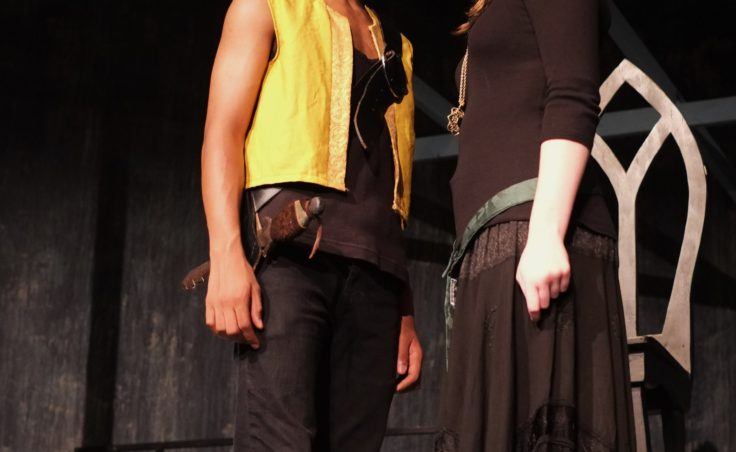 Two actors pose onstage
