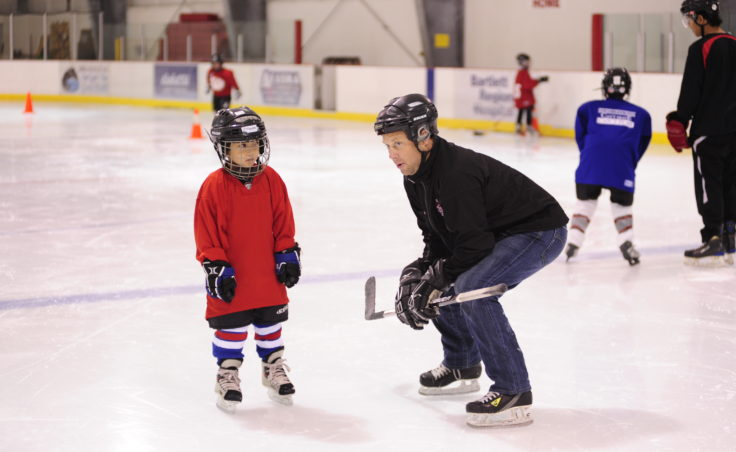 JDIA coach Jason Kolhase greets a newcomer to the ice at the youth hockey association's Learn to Play event Saturday.