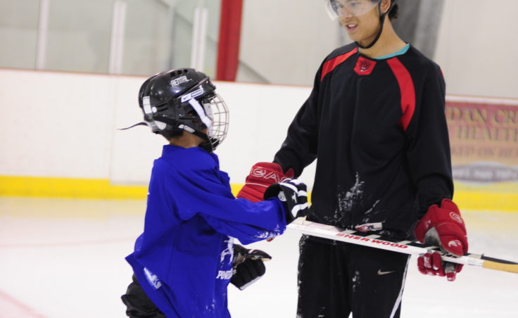 Former Juneau Douglas High standout Tod Baseden spends time with a boy who wants to learn how to play hockey Saturday at Treadwell Ice Arena.