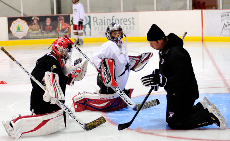 Chad Macleod (right) works with goalies Kyle Robinson (black jersey) and Wolf Dostal (white jersey) throughout the week at the Rocky Mountain Hockey School.