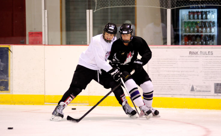 Emma Kaelke and Gavin Murhpy battle for the puck while attending the Rocky Mountain Hockey School at Treadwell Ice Arena.