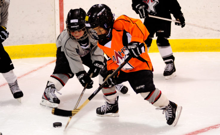 From left, Oliver Stopher and Dylan Sowa battle for a puck while working on a drill at the Rocky Mountain Hockey School.