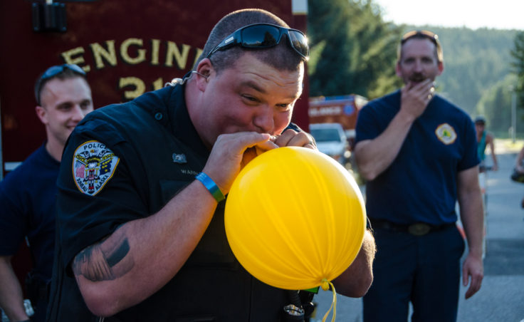 Officer Steve Warnaca blows up a balloon for kids at the block part