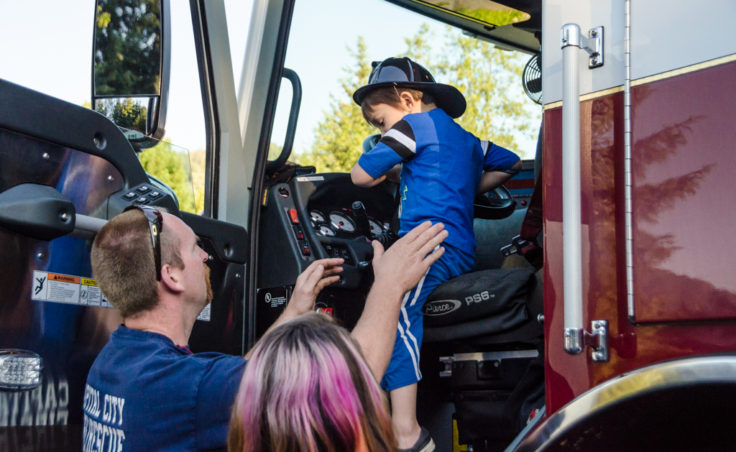 Firefighter Craig Brown helps Tristan Winchell, 4, from the front seat of Engine 31.