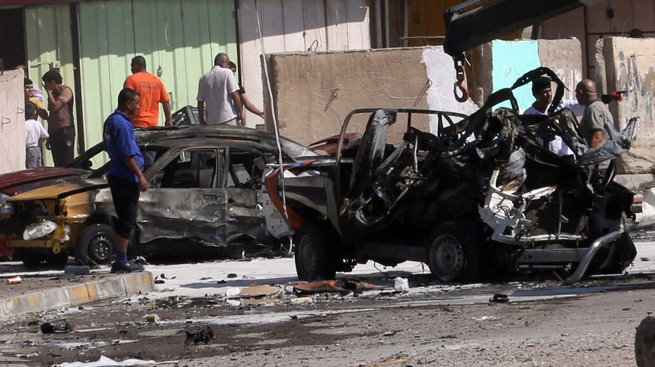 Iraqis look at the site of a car bomb attack in Baghdad, where at least 10 car bombs were detonated during the city's rush hour Monday. Khalid Mohammed/AP
