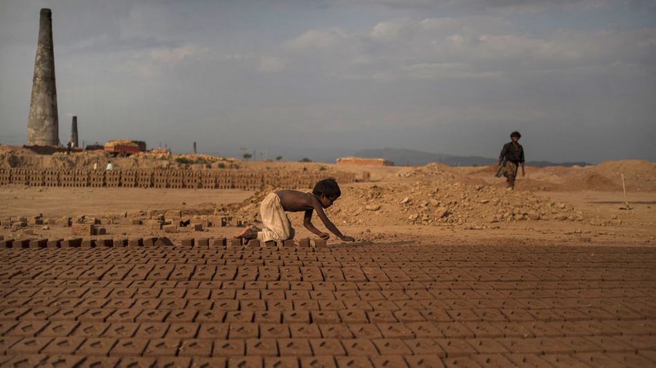 Near Islamabad, Pakistan, 6-year-old Jabro Mounir was arranging bricks this summer — part of his daily work at a brick-making facility. He earns a little less than $2 per day. Muhammed Muheisen/AP