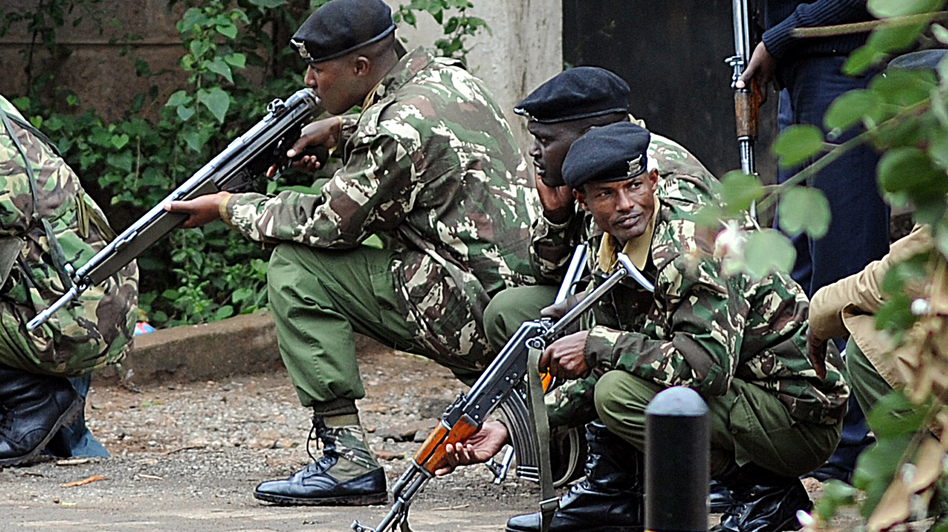 Kenyan police officers take cover outside the Westgate mall in Nairobi on Monday. Simon Maina /AFP/Getty Images