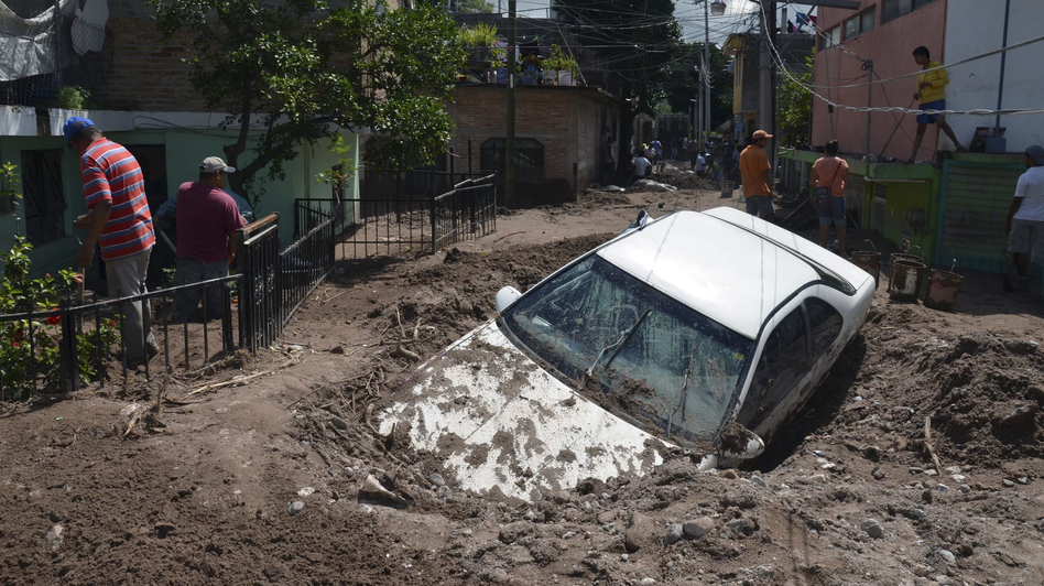 A car lays buried in mud after flooding triggered by Hurricane Manuel in Chilpancingo, Mexico. Alejandrino Gonzalez/AP