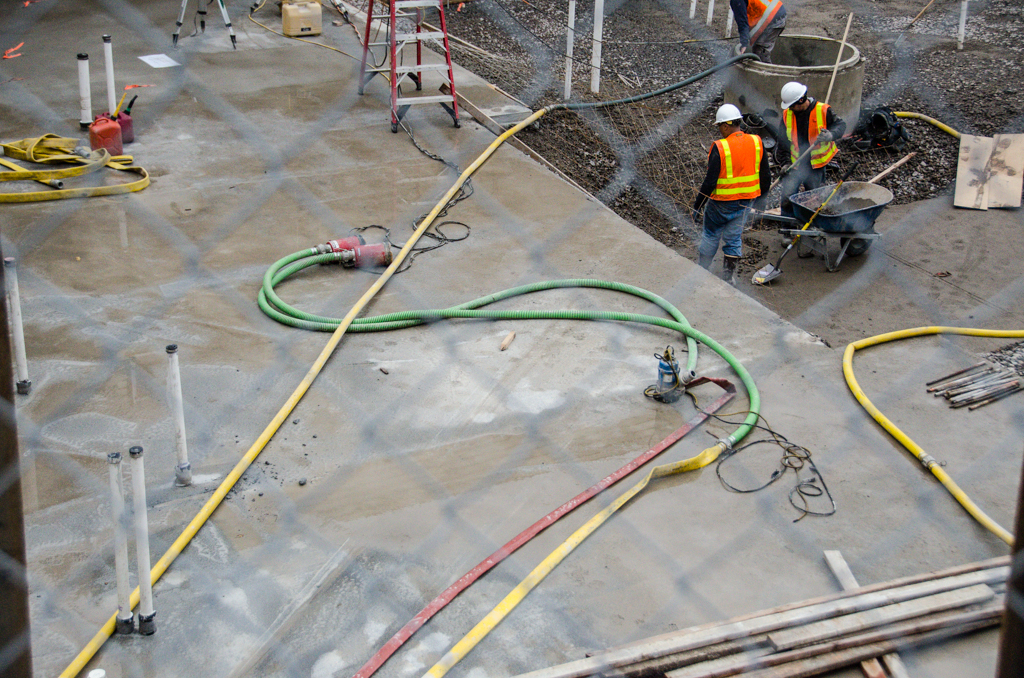 Pumps and hoses are spread throughout the construction site to deal with excess water.