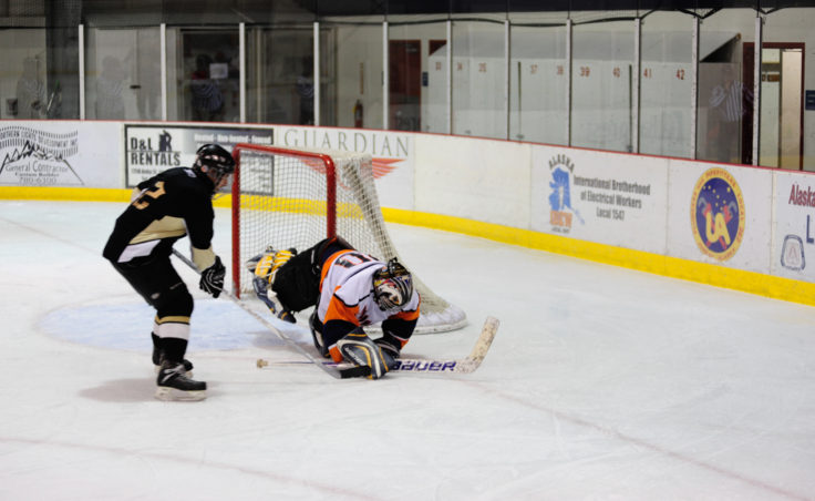 Island Pub goalie Thomas McKenize pounces on a puck just as the Viking's Rich Morris descends on the goal during a Tier A game on Sunday.