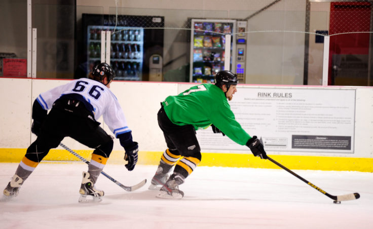 Jared Pique (left) of Alaska Airlines keeps Mason Morriss from getting close to the net in a game against the Green team during a Tier A match on Sunday. Morriss' team, however, lead his team to a 4-3 victory with a hat trick in the JAHA opener.