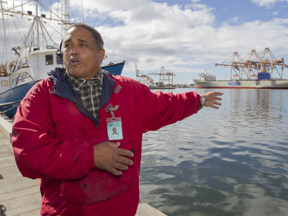 John Hernandez of Kailua, Hawaii, who owns John's Fresh Fish, is shown on Thursday. In the background at right is a container ship owned by Matson Navigation Co. A pipe maintained by the company cracked and caused the molasses spill. Eugene Tanner/AP