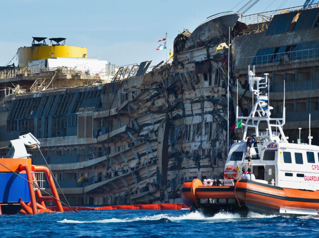 A Coast Guard patrols in front of the severely damaged right side of the Costa Concordia cruise ship after it was righted last week. Marco Secchi/Getty Images