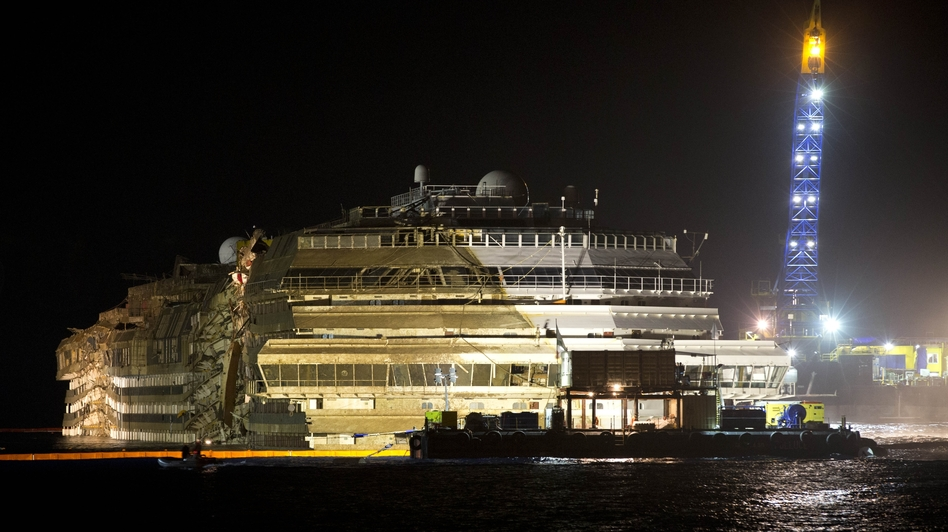"The Costa Concordia is seen after it was lifted upright on the Tuscan Island of Giglio, Italy, early Tuesday morning. Officials declared the results of the 19-hour operation ""perfect."" Andrew Medichini/AP"