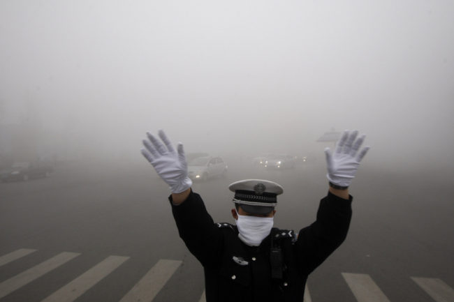 A policeman gestures as he works on a street in heavy smog in Harbin, northeast China's Heilongjiang province, on Monday. AFP/AFP/Getty Images