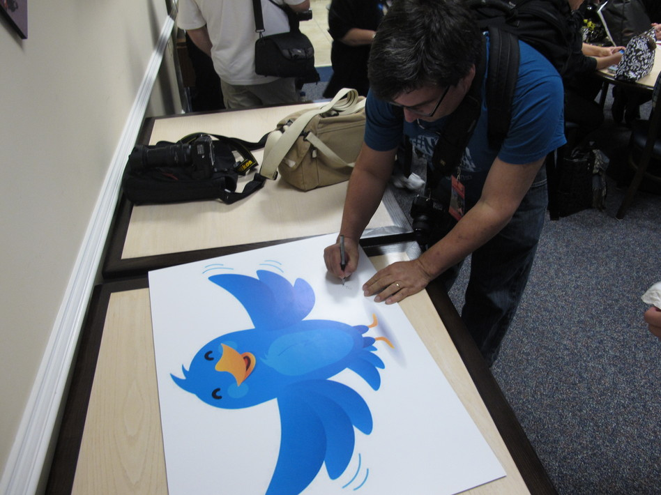 In this Nov. 8, 2011, photo, NASA fan David Parmet signs his name on a Twitter logo during a tweetup event for about 50 of NASA's Twitter followers at the Langley Research Center in Hampton, Va. Brock Vergakis/AP