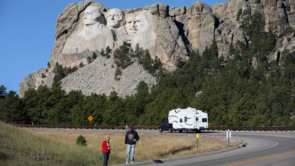 Tourists stop on the roadside near Mount Rushmore, after their visit was canceled due to the government shutdown. South Dakota and other states have reached an  agreement to fund operations to reopen the parks. Scott Olson/Getty Images