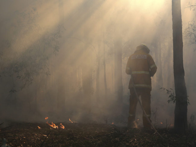 Flames flicker near Bilpin, Australia, as a firefighter finishes securing the area on Wednesday. Rob Griffith/AP