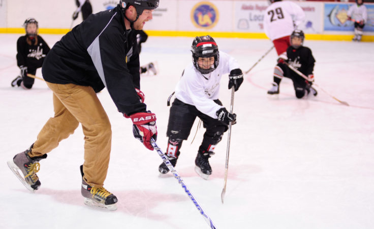 JDIA Coach Matt Boline has some fun with Ilya Wallace during a puck handling drill.