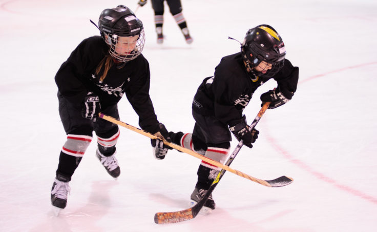Minta Schwartz, left, and Mac Brna chase down a puck during a drill at JDIA's skills development camp.