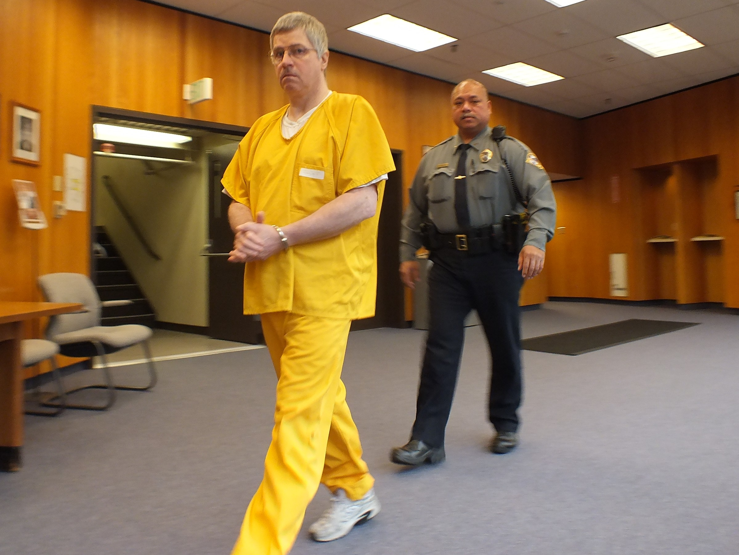 Robert Kowalski (left in yellow) walks under escort by a Judicial Services officer to a hearing at the Dimond Court Building. Photo by Matt Miller/KTOO News