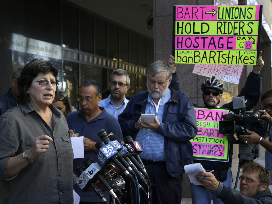 Roxanne Sanchez, left, president of Service Employees International Union Local 1021, left, speaks during a news conference on Thursday in Oakland, Calif.    Ben Margot/AP