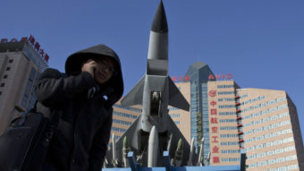 Concerns over China's air defense claims led Secretary of Defense Chuck Hagel to call Japan's defense minister Wednesday. Here, a man makes a call near a replica of a Chinese fighter jet displayed in Beijing Wednesday. Ng Han Guan/AP