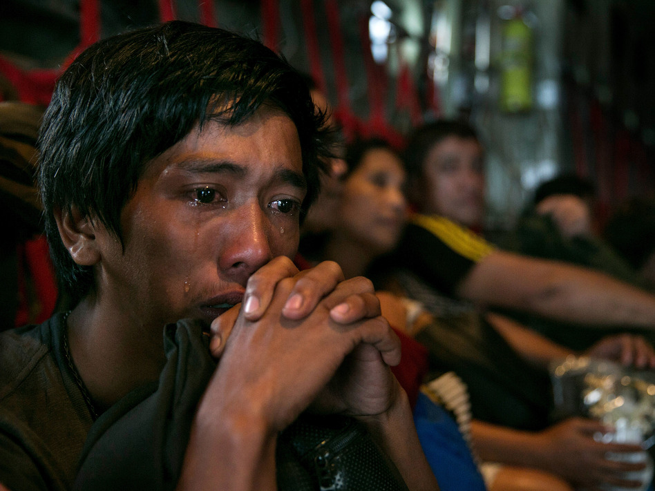 In anguish: Tears ran down the cheeks of a man as he waited with other survivors Tuesday for a flight out of Tacloban, the Philippines, which was devastated by Typhoon Haiyan. Paula Bronstein/Getty Images