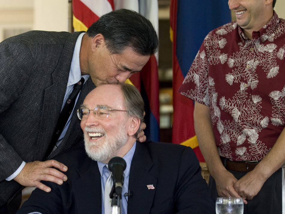 Hawaii state Sen. Clayton Hee playfully gives Gov. Neil Abercrombie a kiss on the head before he signs the Hawaii Civil Unions bill into law at a ceremony in February 2011 in Honolulu. Eugene Tanner/AP