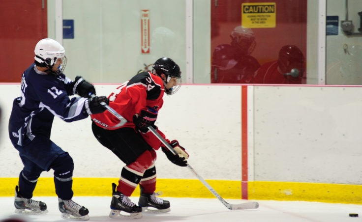 Juneau defenseman Chase Barnum evades Soldotna's Bob Lott in a weekend series at Treadwell Ice Arena.