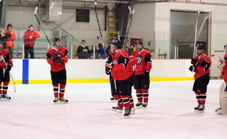 Juneau's hockey players close out each night by raising their sticks in a salute to the fans.