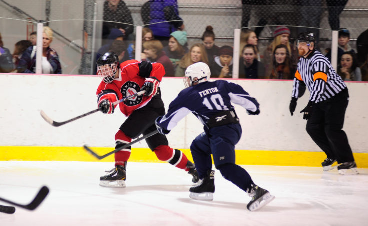 Juneau left wing Cole Cheeseman unleashes a shot in a crowd of opposing players from Soldotna during the team's season opening series versus Soldotna at Treadwell Ice Arena.