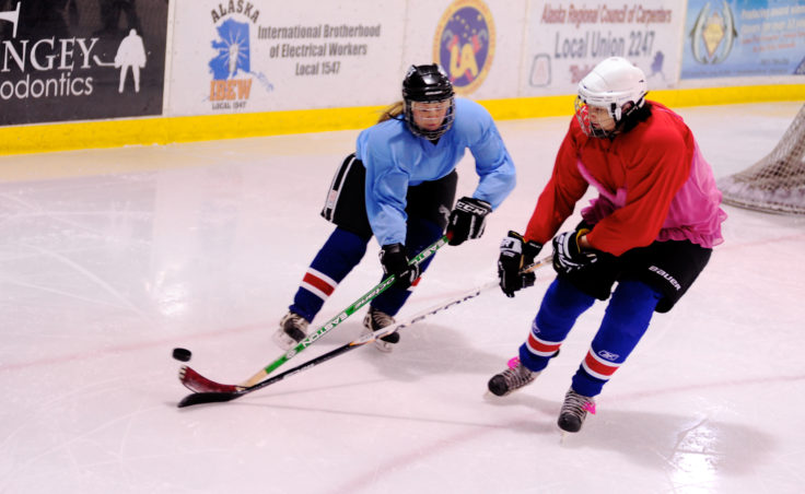 Caroline Schultz (blue) and Emily Hutchison battle for the puck to the left of the net during the 10th Annual Jamboree women's hockey tournament at Treadwell Ice Arena.
