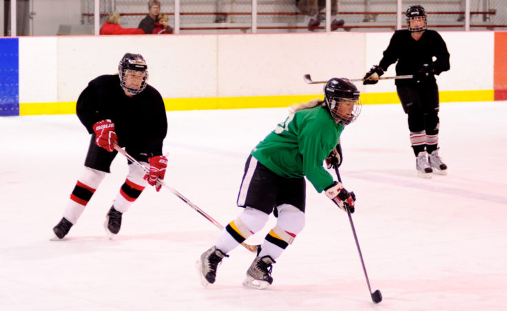 Wendy Smith (left) chases Leslie Slater across mid-ice during weekend competition of the 10th Annual Jamboree women's hockey tournament at Treadwell Ice Arena.