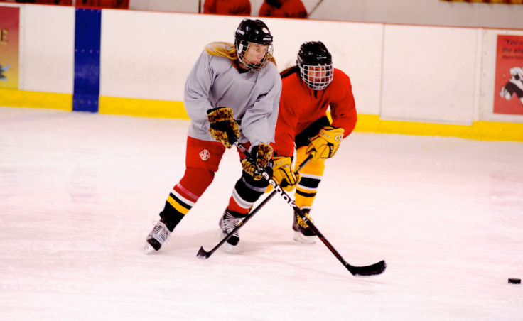 Deb Mosley (left) and April Sapp compete for a loose puck during the 10th Annual Jamboree women's hockey tournament at Treadwell Ice Arena.