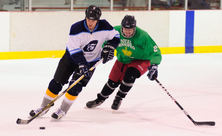 Winnipeg's Shane Carson stays close to Alaska Airlines defenseman Jared Pigue in a B Tier title game.