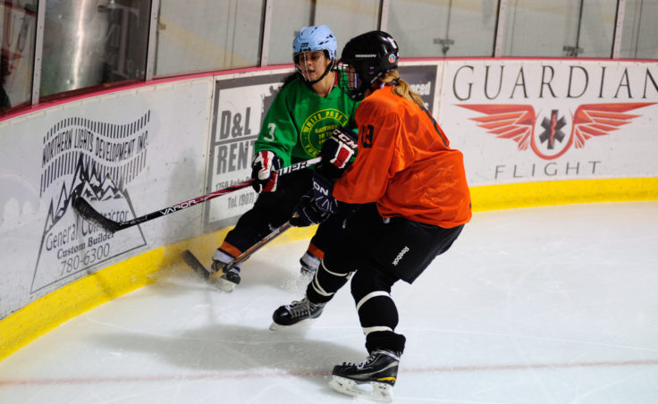 Christy Hartman (left) and Eliza Dorn converge in the corner for a loose puck during a Tier W title game between Hartman's Yukon Pass and Dorn's Shamrock's teams.