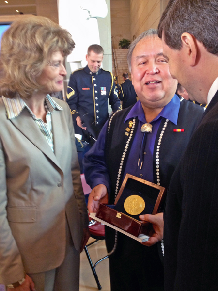 Ozzie Sheakley hold the Congressional Gold Medal awarded to the Tlingit Tribe for code talking service during World War II. He speaks to Sens. Lisa Murkowski and Mark Begich after the ceremony. Photo by Liz Ruskin, APRN – Washington DC.