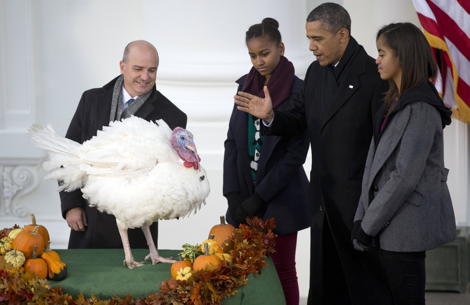 President Barack Obama, with daughters Sasha, second from left, and Malia, right, bestows a presidential pardon on Popcorn, the turkey, in a White House Thanksgiving tradition. Carolyn Kaster/AP
